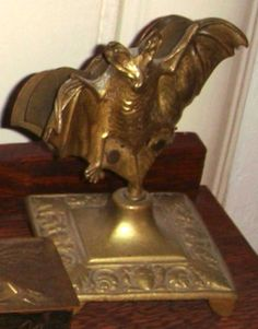 Late Victorian figural brass bat calling card / letter holder. Base with scrolled foliage and masks.