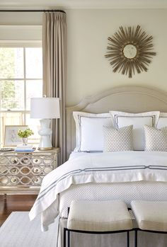 Classic bedroom style with neutral upholstered headboard, mirrored bedside table and gold sunburst mirror above the bed.