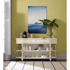 Showcase charming cottage or coastal style with this console table. The table's spindle legs and paneled back exude casual coastal style, enhanced by a distressed white finish. Two drawers and two shelves provide storage and display space perfect for any living room or hallway.