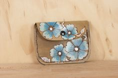 A tiny piece of functional art, the handmade leather Belle Stitched Pouch has western inspired wild roses on it in turquoise and brown. Perfect for keeping loose change, jewelry, or any small items you don't want floating at the bottom of your purse, or you can even use it as a small wallet on its own.