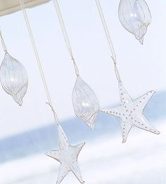 Icy Glass Ornaments  -- Glittering in the sunlight with an almost icicle-like appearance, purchased glass-seashell ornaments hang from varied lengths of sheer ribbon. Although these ornaments are pretty on a Christmas tree, they are especially effective hanging at a window