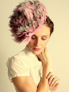 Tocado especial para una mujer femenina. Flor elaborada con plumas de cuello de gallo sobre base de sinamay.