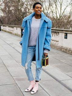 Donna Wallace wearing an oversized blue coat, grey crew neck sweater, and cuffed ripped jeans