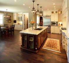 White granite, cherry cabinets for the island and white cabinets for the perimeter. Open floorpolan with lots of lighting. (Granite- Siena Bordeaux/White Spring/ Monte Carlo Bordeaux). Visit globalgranite.com for your natural stone needs.
