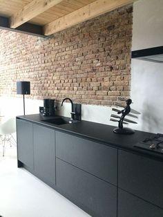 Ladrillo a la vista, techos de madera y muebles de cocina en color negro