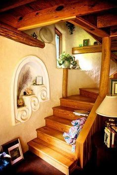 """Love this """"stepped"""" wall niche alongside the staircase here... what a great detail! Designing unique features like this is one of the best parts of building with cob or straw bales. (Source: Livia O.) - via: The Year of Mud (fb)"""