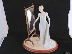 Franklin Mint figurine entitled 'Emma' from the 'Jane Austen' series.  It depicts a young lady in a long white dress holding a fan admiring herself in front of a mirror. Mirror is freestanding and not attached to the figurine.  It is a limited edition of 9,500.