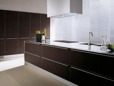 Long sleek handles from edge to edge mounted at the very top of the drawers seems modern and understated.
