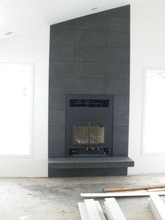 Black flat tile around wood burning fireplace #fireplace