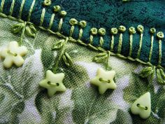 detail of french knots, stem stitch, and buttons