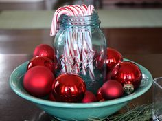 simple and sweet - candy canes in a mason jar surrounded w red ornaments