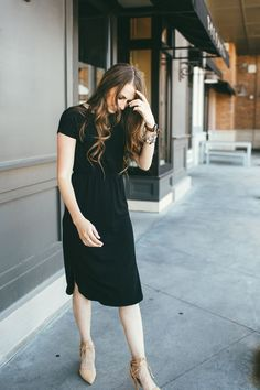 Girl with long brown hair curled wearing black dressed with rouched waist band and nude heels that tie around the ankle with arvo watch and alex and ani bracelets stacked