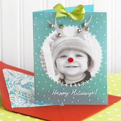 Santa's Little Helper Christmas Card : Add a special holiday touch to a plain photo card with a transparency layer, ribbon, and jingle bells. Cut a circle from a black-and-white photo of your child. Adhere to the center of an 8-1/2x5-1/2-inch piece of teal cardstock, folded in half. Cut a 5-1/2x4-1/4-inch rectangle from a transparency sheet.