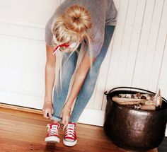 Red all star convers , bandana , bun , skinny jeans , plain gray sweater .