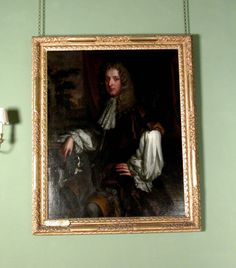 Oil painting on canvas, John Lovelace, 3rd Baron Lovelace (c.1638/42-1693) by Sir Godfrey Kneller, Bt (Lübeck 1646 - London 1723), circa 1660-70. A seated three-quarter length portrait of a man, turned to the left but facing, previously called Sir Edward Rice (1631- 1664) in a dark russet suit and lace cravat. His right arm rests on a table on the left and his spaniel appears below. Beyond, on the left is a landscape and figures. Another version is at Attingham Park.