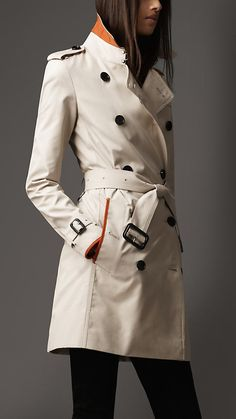 Burberry Trench Coat. Description: Cotton blend trench coat with set-in sleeves and vibrant piped trim. Referencing the original Burberry trench coat, heritage features include epaulettes, gun flaps, rain shield, D-rings, belted waist and cuffs.    Love the piped orange detail. Yum.