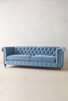 An oversize chesterfield sofa upholstered in denim blue colored velvet. Proudly…