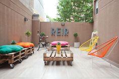 Primavera: ¡tiempo de patio! Aquí, uno con sillones y mesas hechas de pallets reciclados y sillas tipo Acapulco en colores brillantes.