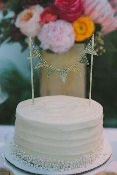 gold bunting wedding cake http://www.weddingchicks.com/2013/09/16/malibu-beach-wedding/