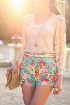 White lace shirt, cream sweater, and floral shorts.