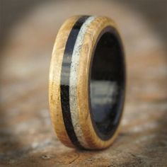 This is an unusual design incorporating Bog Oak from Ireland and white sand from Iona, the Scottish Hebridean Island. This design was request by a customer as a wooden engagement ring to reflect their Irish and Scottish heritage. To see more wooden ring designs visit www.wooden-rings.com