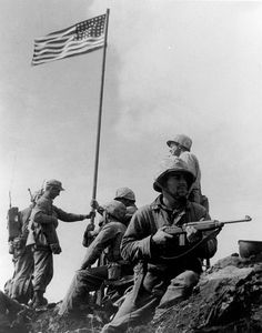 """First Flag Raising on Iwo Jima.  Here is the real flag raising shot, raised atop the mountain soon after it was captured early in the morning of Feb. 23, 1945. Captain Dave Severance was ordered by 2nd Bat. Cmdr. Chandler Johnson to send a platoon to go take the mountain. """"Severance, the commander of Easy Company, ordered 1st Lt. Harold Schrier to lead the patrol. Just before Schrier was to head up the mountain, Cmdr Johnson.  handed him a flag saying, 'If you get to the top, put it up.'"""