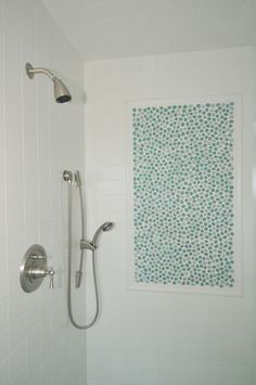 Kid's bathroom shower with white ceramic tile on the wall and an insert of glass pebble tiles. There is a handheld showerhead on slide bar mounted to the wall.