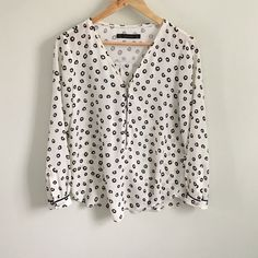 """Zara Long Sleeve Printed Top With Front Zip Pretty, flattering ivory blouse with black overall print and front zip. Looks as cute over jeans as with slim black pants. Not sure of fabric but has a rayon feel. Overall length about 24"""". Piping at cuffs and back; pretty metal stud closures at cuffs. Zara Tops Blouses"""