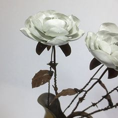 "A Single Rustic White Immortal Wild Rose With Barbed Wire Stem Forever Blooming Flower. What better way to express your love than with a beautiful wild rose that will never die! This rustic metal rose won't fade with time or die of neglect. If treated kindly it will last for generations. The blossom is about 3"" across with 5 layers of hand shaped metal petals. It has a vintage and rusty barbed wire stem that is around 18"" long. With a leaf that I shaped from an rusty old tin can. This…"