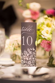 Le Meridien Philadelphia hosted this romantic wedding where soft blush tones and sage green flowers filled glass vases a top bold black and white linens. Votive candles illuminated custom table numbers created by ALH Designs.  Photos courtesy of Main Line Wedding Photography + Cinema