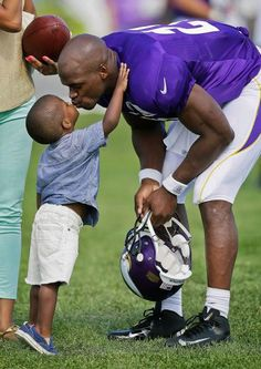 Minnesota Vikings running back Adrian Peterson gets a kiss from his son Adrian Jr. at the end of practice at NFL football training camp on Monday in Mankato, Minn. (Charlie Neibergall/AP)
