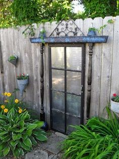 Garden Salvage - Secret door to no where - old door mirrored and mounted to the fence..