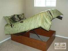 Make a platform bed more amenable to storage by adding a hinge, some shocks, and a fulcrum about two feet from the head to allow the mattress to bend. Also don't forget the divider near the top to allow for some small measure of organization.