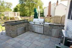 This outdoor kitchen and bar area was constructed with Techo Bloc mini creta plus wall system which is complimented by the Techo Bloc 'Blu' patio in Champlain Grey.