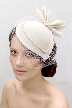 So, what exactly is a fascinator? Running the gamut between large clips to very small hats, fascinators also come in a wide variety of styles. Most popular in the UK, fascinators are also used in the South, where more traditional moms and wedding guests have adopted them. This cream-colored wool fascinator could work well for a city hall bride or for a mother of the bride in a suit.