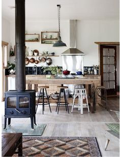 Rustic kitchen with pot belly stove, light wood floors.