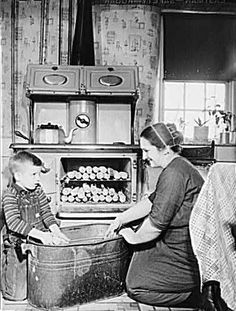 1946 in Lititz, PA--Mennonite Farmer's wife and son husking corn.