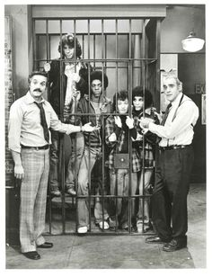 A promo photo (from 1975?) of the Sweathogs (from Welcome Back Kotter) on the set of Barney Miller taken at ABC Television Center in L.A. L-to-R: Hal Linden, John Travolta, Lawrence Hilton-Jacobs, Ron Palillo, Robert Hegyes, Abe Vigoda.