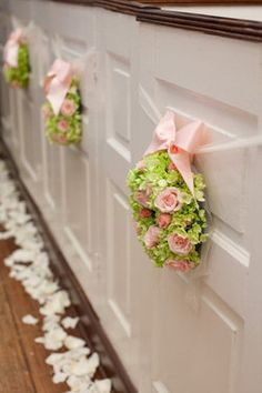 This is so lovely... I really like the idea of wreaths tied to the pews, with rose petals on either side.