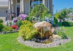 Ein kühles Wasser-Brunnen von einem großen Felsen gibt einen schöner Blick. Um seine Kanten sind Steine und Gräser während blühende Moppbezügen und Petunien gibt Leben auf der Rückseite.
