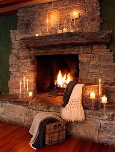 """Rustic stone fireplace ... its hearth and reclaimed wood beam mantel are """"warmed"""" by the addition of candles, blankets, and baskets."""