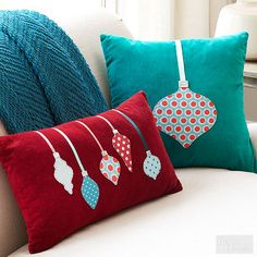 Embellish pillow covers for festive decor that doesn't sacrifice on function. Remove velvet covers from purchased pillows. Using a hot, dry iron, fuse medium-weight interfacing to the back of selected patterned fabrics. Download ornament patterns and trace onto interfacing side of fabric; cut out. Arrange and pin ornament shapes as desired; hand-stitch to pillow covers. Cut assorted ribbons in lengths to reach top seam of pillow cover; adhere with fabric glue. For ornament caps, cut silver…