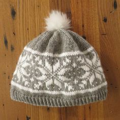 This little beanie is a quick knit in worsted weight yarn and features a classic snowflake motif. Top it off with an easy to make faux fur pom-pom.