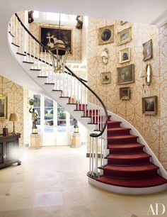 In a Mississippi house decorated by Richard Keith Langham, Clarence House wallpaper enlivens the stair hall, which is decorated with antique dog portraits and a Regency-style lantern  https://yofromutu.be/HojAo1Nn-Dw & Co.