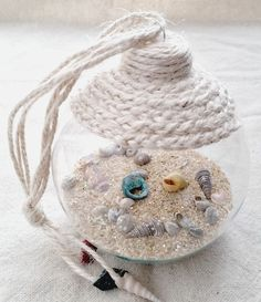 An easy craft tutorial on how to make a beach in a glass coastal ornament. A great way to show off shells collected during the summer.