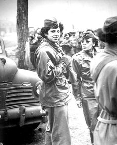 WWII African American WACs - The `Top-Kick' looks them over at Camp Shanks, NY, Transportation Corps staging area of the Port of Embarkation. 1945.