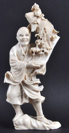 AN EARLY 20TH CENTURY JAPANESE MEIJI PERIOD IVORY OKIMONO depicting a male holding a large carp. Minor faults. Signed. 9.5ins high.