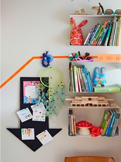 View of noticeboard and shelving with children's books, toys and accessories in colourful kids' room.