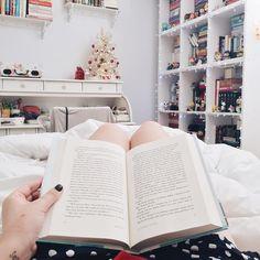 Lendo na cama mostrando a estante de livros e a escrivaninha com decoração de Natal.