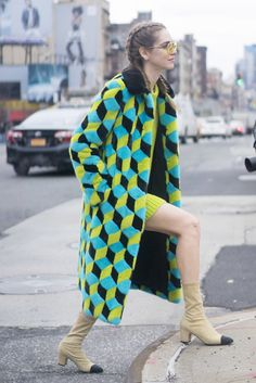 A graphic green coat paired with Chanel boots.